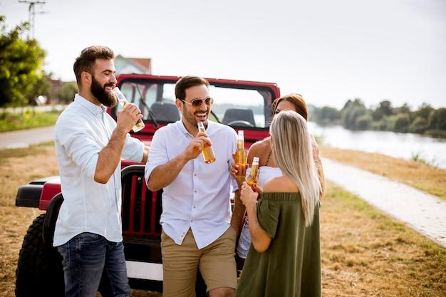 屋外の車で飲んで楽しんでいる若者のグループ