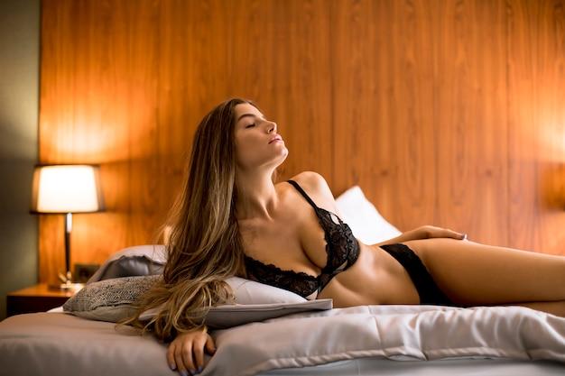 自宅の寝室のベッドの上に敷設美しい若いブルネットの女性