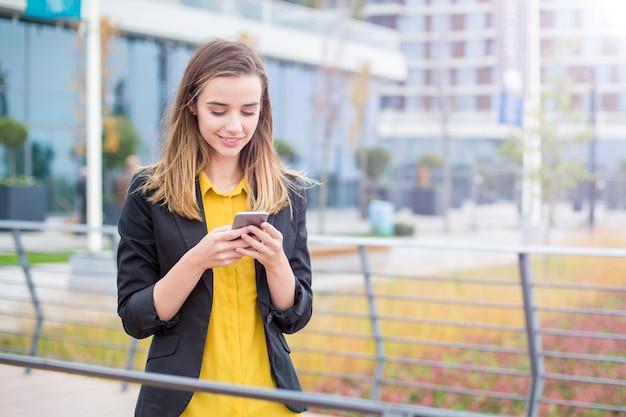 Исполнительный работает с мобильным телефоном на улице с офисными зданиями