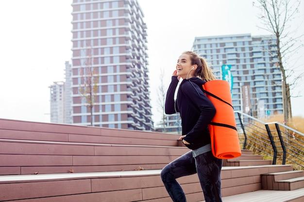 屋外の背中にマットで歩くフィットネス女性