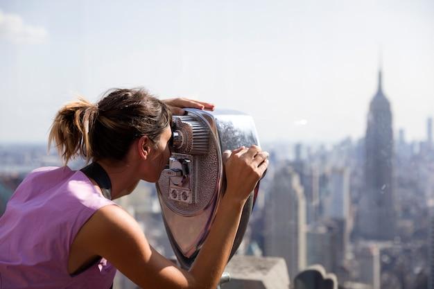 女性観光客が双眼鏡で今ニューヨークに見える