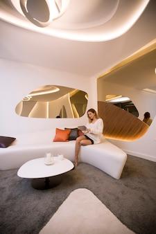 Молодая женщина с планшетом сидит в роскошной квартире