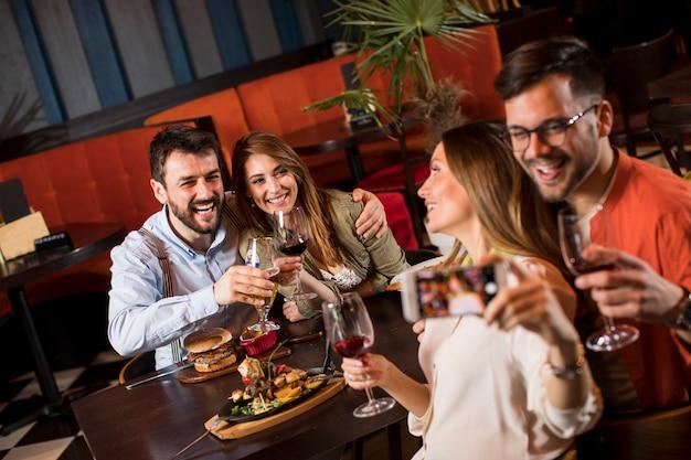 Красивые молодые друзья, делающие селфи и улыбающиеся, обедая в ресторане