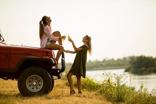 Две счастливые молодые женщины пьют сидр у машины на берегу озера