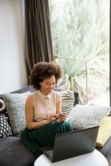 Привлекательная молодая женщина работает на ноутбуке и с помощью мобильного телефона в домашних условиях