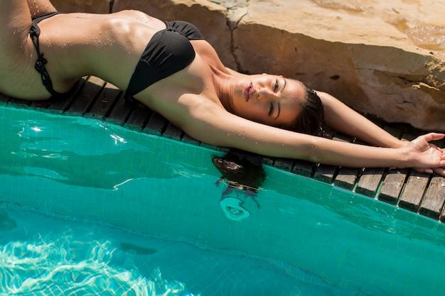 プールのそばに敷設の若い女性