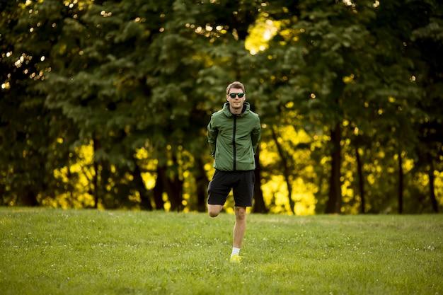 日当たりの良い緑豊かな公園でトレーニングをしながら実行している運動の若い男
