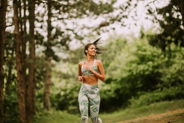 Молодая женщина фитнес работает на лесной тропе