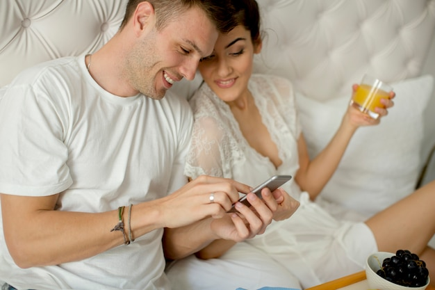 ベッドで朝食を持っていると携帯電話を見て若いカップル