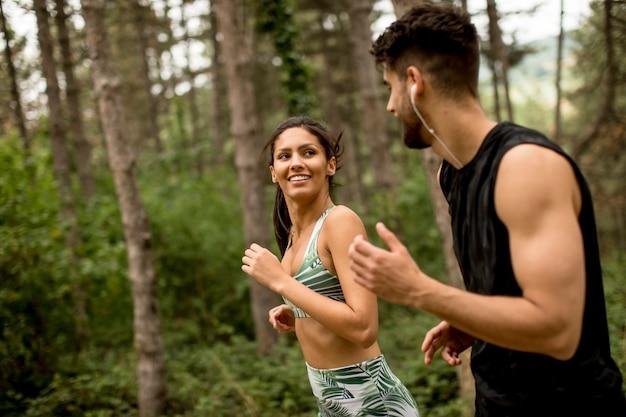Молодые пары фитнеса бежать на лесной тропе