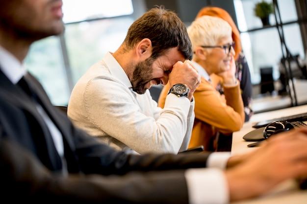 ストレスの下で若いプロのビジネスマンがオフィスでの仕事にコンピューターを使用してください。