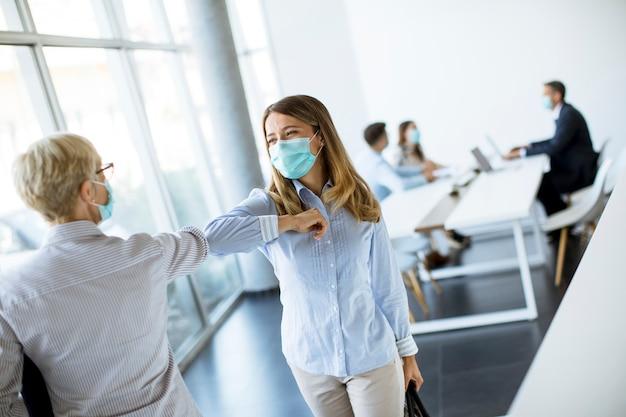 Женщины-коллеги держат социальную дистанцию в офисе, приветствуют друг друга, ударяя локтями, предотвращая распространение скрытой коронавирусной инфекции.