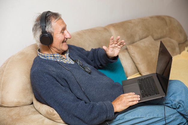 イヤホンで自宅に立地し、オンラインビデオ通話を持つ現代の老人