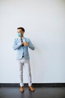 防護マスクを持つ若くてスタイリッシュなビジネスの男性がオフィスの壁に立っています。