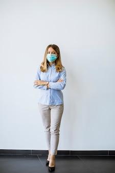 防護マスクとささいな若いビジネス女性がオフィスの壁に立っています。
