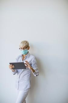 ハンドヘルドデジタルタブレットとウェアマスクを使用してコロナウイルスによる感染を防ぐ成熟した実業家