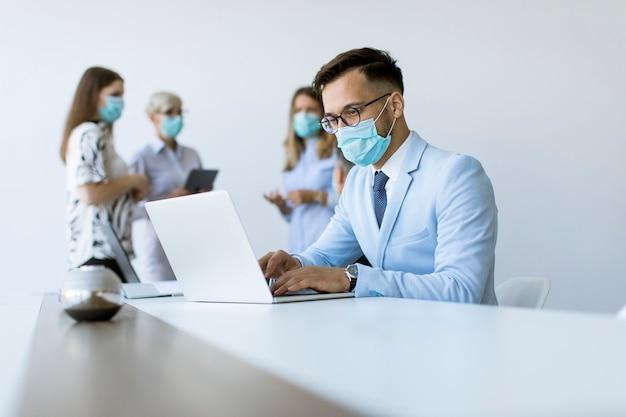 医療用防護マスクを持つ若いビジネス男はオフィスでラップトップで動作します