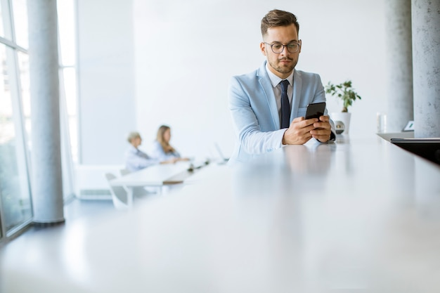 オフィスで彼の携帯電話を使用して、バックグラウンドで働いている彼の同僚ながら笑顔幸せな若い男