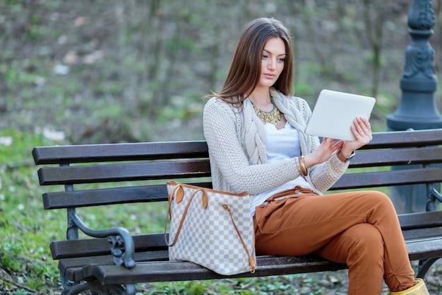 公園でタブレットを持つ若い女