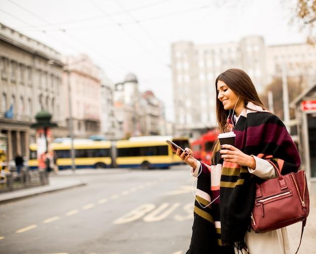 Молодая женщина, приветствуя такси на улице в городе