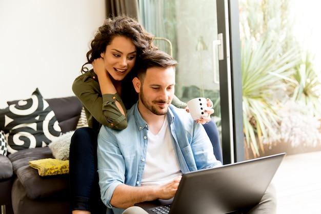 Молодая пара, сидя на полу и используя ноутбук.