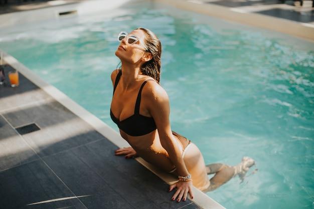 若い、魅力的な女性は、夏の間に屋外プールで楽しむ