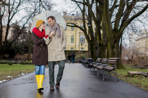 ロマンチックなカップルは雨の中を歩いている