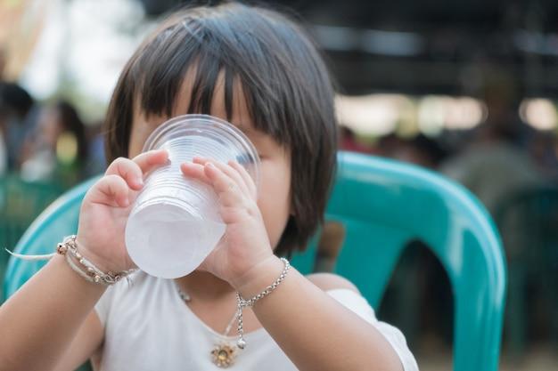 子供の女の子はガラスプラスチックで水を飲む。