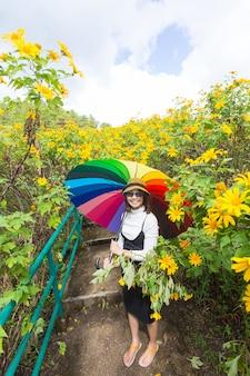 アジアの女性は多色の傘を保持します。