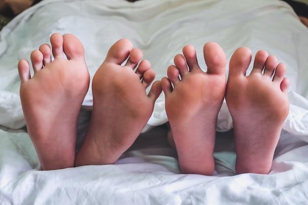 ベッドと寝室でセックスを持っているカップルの上で男性と女性の足のクローズアップ。