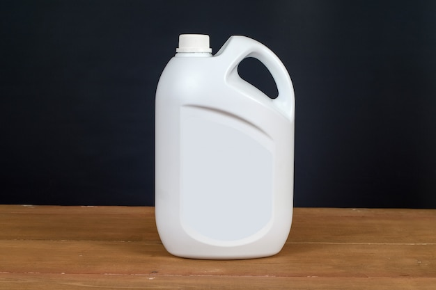 Белый контейнер пластиковой бутылки на деревянный стол.