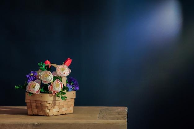 テーブルの上のバスケットにピンクのバラのある静物。