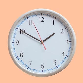Аналоговые настенные часы на цветном фоне.