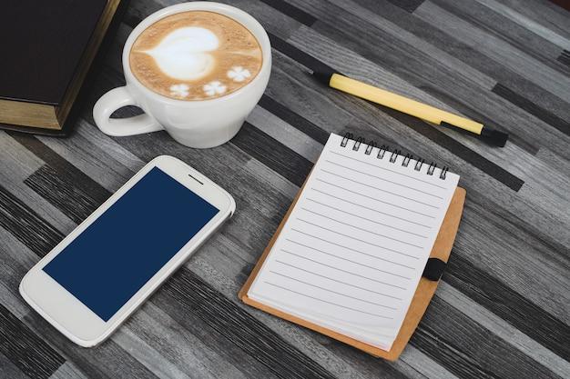本のメモ、スマートフォン、オフィスのテーブルの上のコーヒー