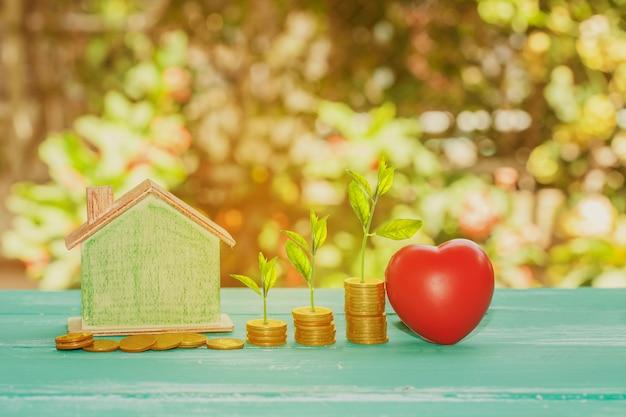 赤いハートの家モデルと自然の背景にコインの小さな植物スタックを成長させます。物件のコンセプト