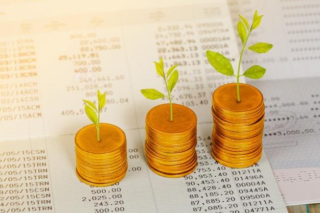 本の銀行と積み上げたコインで小さな植物を育てます。