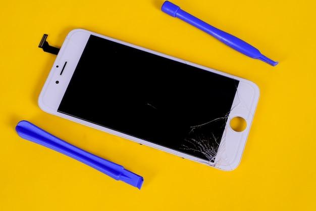 背景に壊れた、ひびの入った液晶携帯画面。