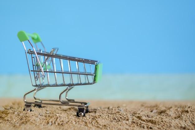 Падение магазинной тележкаи на тропическом пляже песка.