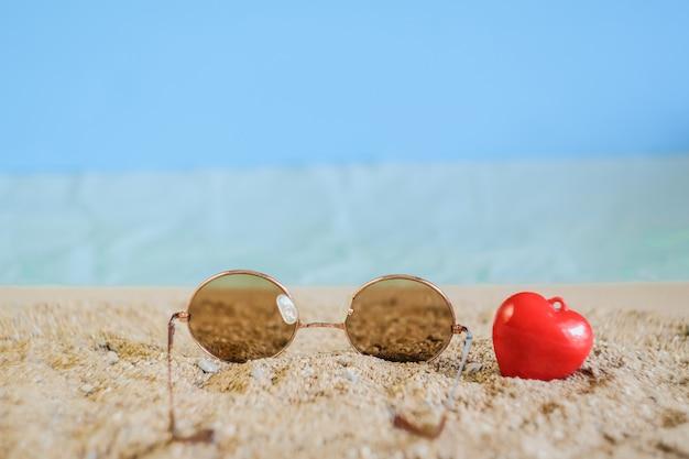 Солнцезащитные очки падают на тропический песчаный пляж.