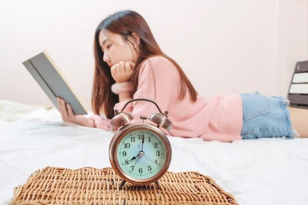 ビンテージアラム時計は、ベッドの部屋で教科書を読んで十代の少女の時間を示しています。