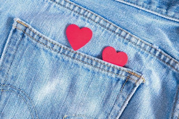 Два красных сердца на фоне старых джинсовых