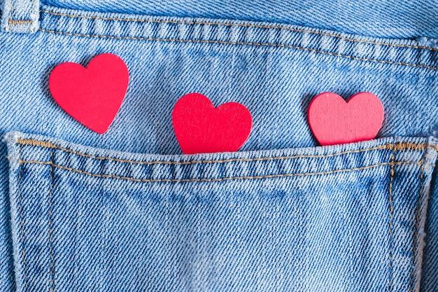 Красные сердечки на старой джинсовой фоне