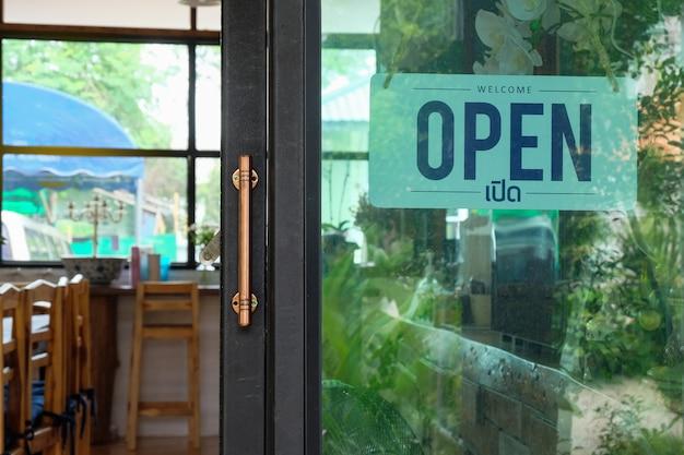 テキストドアのサインを開いて、コーヒーショップのガラスのドアに掛かっています。