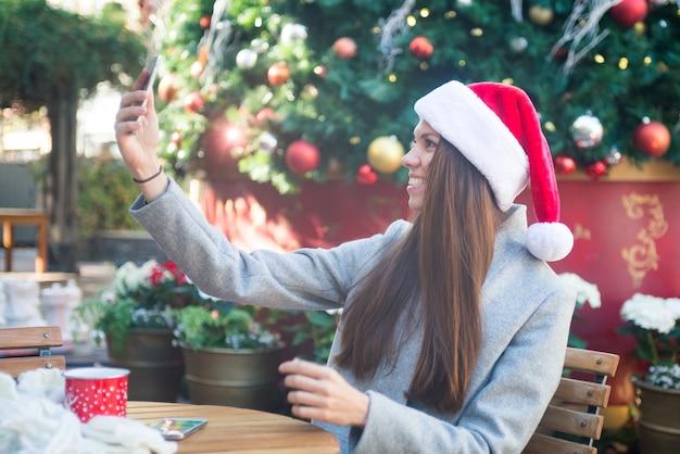 Смех женщина в шляпе санта, занимая себя возле рождественская елка в кафе за пределами