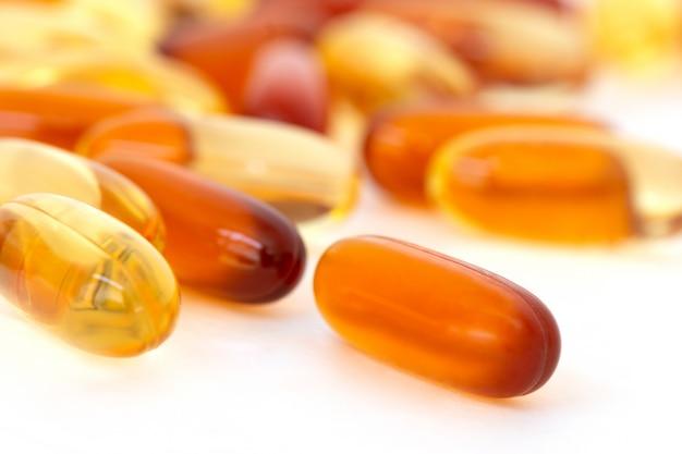 ビタミンと白い背景の上の健康補助食品