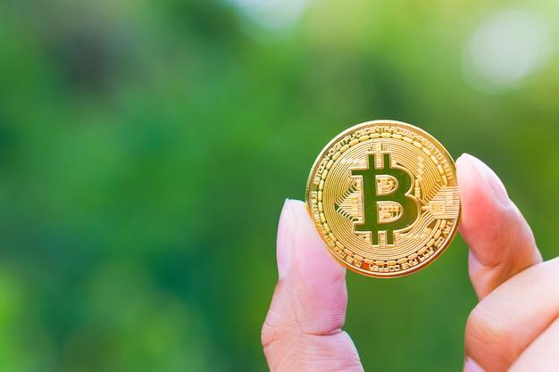 Золотая биткойн-цифровая валюта находится в руках бизнесменов.