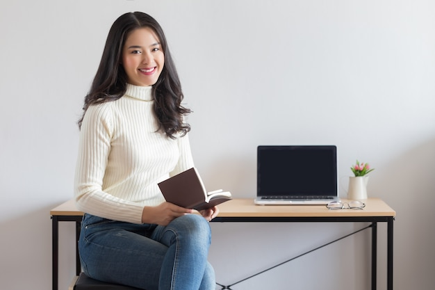 Молодая счастливая азиатская женщина читая книгу