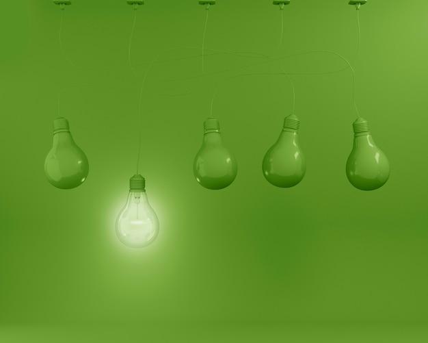 Висячие зеленые лампочки с сияющей одной другой идеей на зеленом фоне. минимальный