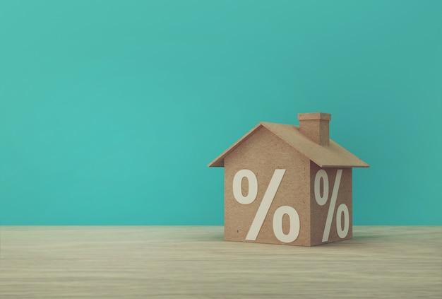 家のモデルペーパーと木製のテーブルにパーセント記号記号アイコンの創造的なアイデア。不動産投資不動産と住宅ローンの金融の概念。