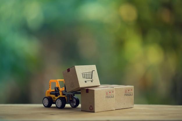 ロジスティックスおよび貨物貨物のコンセプト:フォークリフトトラックは、紙箱でパレットを移動します。